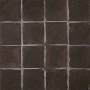 A brown terra cotta stained insert tile by Jeffrey Court.