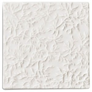 A white ceramic decorative element coral deco tile by Jeffrey Court.