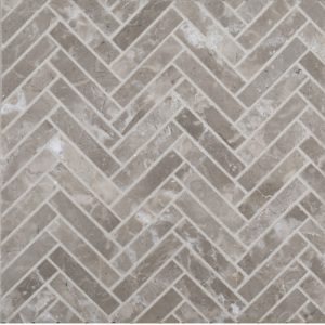A grey natural stone mosaic herringbone styx tile by Jeffrey Court.