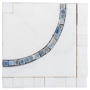 A white natural stone border/listello city line corner tile by Jeffrey Court.