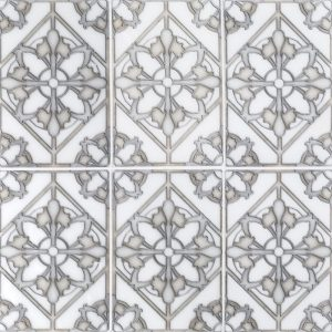 A white natural stone decorative element floral imprint tile by Jeffrey Court.